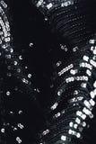 平衡有衣服饰物之小金属片的,假钻石的织品黑人礼服女孩 五颜六色的闪光金属片的纹理 免版税图库摄影