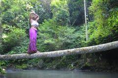 平衡瑜伽位置的可爱的30s白种人妇女在河的稀薄的树干在放松和凝思在美丽的雨 图库摄影