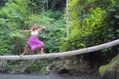 平衡瑜伽位置的可爱的30s白种人妇女在河的稀薄的树干在放松和凝思在美丽的雨 免版税库存图片