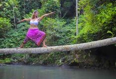 平衡瑜伽位置的可爱的30s白种人妇女在河的稀薄的树干在放松和凝思在美丽的雨 免版税库存照片