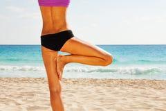 平衡瑜伽位置的女孩的后面身体在海滩 免版税库存照片