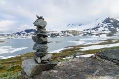 平衡的堆反对多雪的山的石头 免版税库存照片