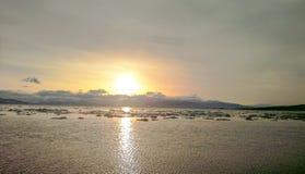 平衡的太阳的日落在海湾的与冰 库存图片