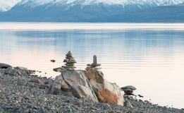 平衡的岩石两个雕塑在湖的支持 免版税库存图片