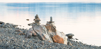 平衡的岩石两个雕塑在湖的支持 免版税库存照片