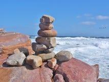 平衡的石堆,在海的海岸的岩石 免版税图库摄影
