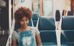 平衡的空的市郊火车蓬松卷发女孩 图库摄影
