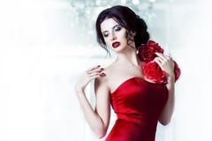 平衡的红色礼服秀丽深色的式样妇女 美好的时尚豪华构成和发型,在背景  免版税图库摄影