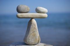 平衡石头 对重量利弊 在冰砾上面的平衡的石头  关闭 免版税库存照片