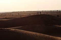 平衡轻的清楚的天空的sanddunes的两个人 免版税库存照片