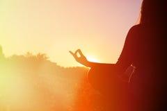平静和瑜伽在秋天实践在日落 免版税图库摄影
