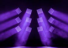 平静和紫色方形的阶段聚光灯与一股烟在音乐会 免版税库存图片