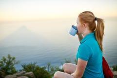 平静地喝她的咖啡的少妇户外 免版税库存图片