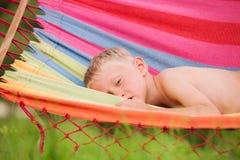 平静地在吊床的小男孩 免版税库存照片