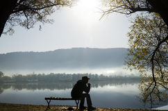 平静地坐在湖旁边的一个人 免版税库存图片