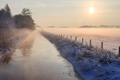 平静的一点结冰的河在黄昏期间的冬天 免版税图库摄影