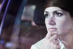 平静的女实业家用在注视着通过车窗城市夜生活,反射光的下巴的手 免版税图库摄影