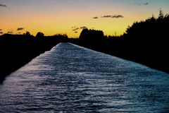 平静的河在清早,日出期间在Methven,新西兰 库存图片