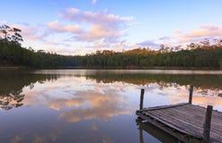 平静的湖的木船坞有日落的 免版税图库摄影