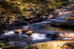 平静的瀑布在秋季轻轻地流动 免版税库存图片