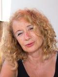 平静的白肤金发的成熟妇女夏天画象  免版税图库摄影