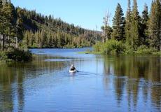 平静的皮船乘驾通过声势浩大的湖 库存照片