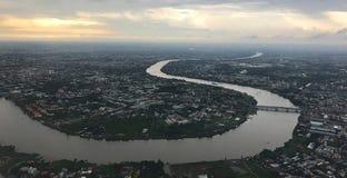 从平面窗口的俯视图:胡志明市和黄昏的蜿蜒的西贡河在一个雨天 图库摄影