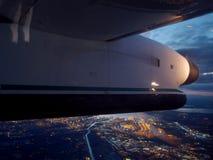 平面翼飞行在市西雅图在晚上 库存图片