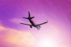平面飞行通过在日出天空的云彩 喷气机 库存照片