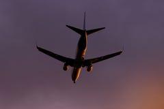 平面飞行通过往日落的云彩在天空 喷气机 免版税库存图片