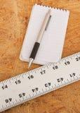 在胶合板顶部的平直的边缘、笔记薄和笔 库存图片