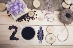 2018年咖啡豆、咖啡杯、木切片和闪烁的题字 库存照片