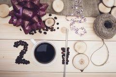 2018年咖啡豆、咖啡杯和木切片,紫色圣诞节弓的题字 免版税图库摄影