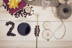 2018年咖啡豆、coffe杯子和木切片的题字 库存照片