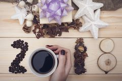 2018年咖啡豆豆的题字和举行一个杯子cofee的手 免版税库存图片