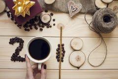 2018年咖啡豆,拿着杯子和木切片的妇女的手指的题字 免版税库存图片