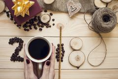 2018年咖啡豆,拿着杯子和木切片的妇女的手的题字 免版税库存图片