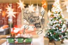 2018年在五颜六色的bokeh迷离背景的新年快乐文本从装饰的圣诞树 免版税图库摄影