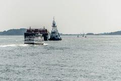 04 09 2017年波士顿马萨诸塞美国遇到波士顿港口的通勤者轮渡通过有拖轮的大货物船 免版税图库摄影