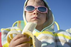 3年男孩在游泳以后吃香蕉 免版税库存图片