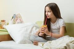 10年的一个困女孩在睡衣的,在床上在家坐并且喝橙汁 免版税库存图片