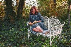 50年的一名严肃的妇女在减速火箭的样式的在有一条白色装饰古色古香的长凳的一个浪漫庭院里读一本书 免版税库存图片