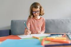 8年的女孩在家坐画与铅笔的沙发文字在笔记本 戴眼镜的在家学习儿童的金发碧眼的女人 免版税库存图片
