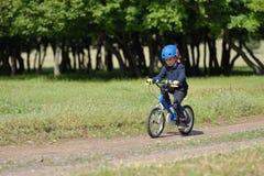 5年的愉快的孩子男孩获得乐趣在有一辆自行车的春天森林在美好的秋天天 活跃儿童佩带的自行车盔甲 库存图片