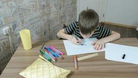 7年的男孩绘他的与蓝色毛毡笔的油漆在坐由桌的有斑纹的纸 股票录像