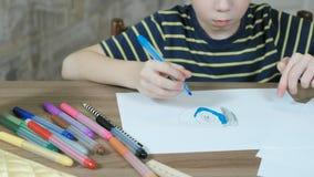 7年的男孩绘他的油漆与一支蓝色毛毡笔的图片在白皮书 股票录像