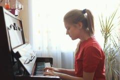 年纪白肤金发的十几岁的女孩的14年在家弹钢琴 图库摄影