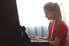 年纪白肤金发的十几岁的女孩的14年在家弹钢琴 库存图片