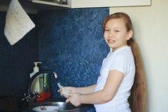 年纪青少年的女孩的12年的画象在厨房洗着盘子 图库摄影