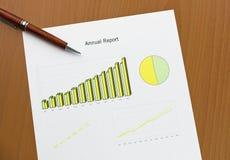 年终报告图表打印,在服务台上的笔。 免版税库存图片